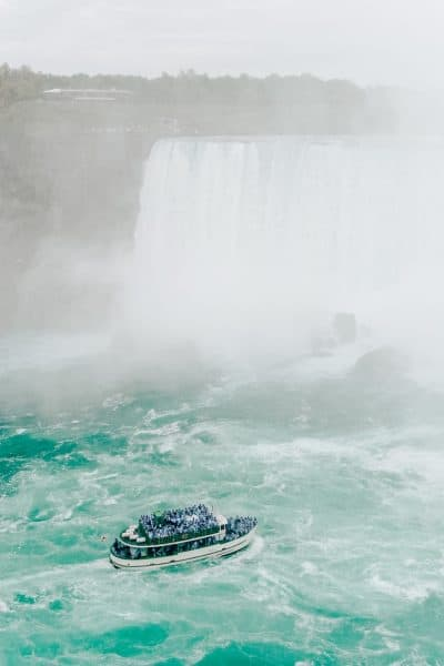 niagara falls and boat full of people on river in mist major canadian american landmark