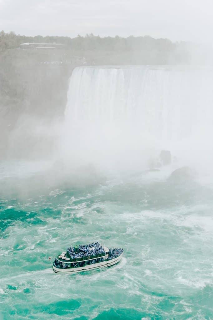 niagara falls and boat full of people on river in mist major canadian american landmark