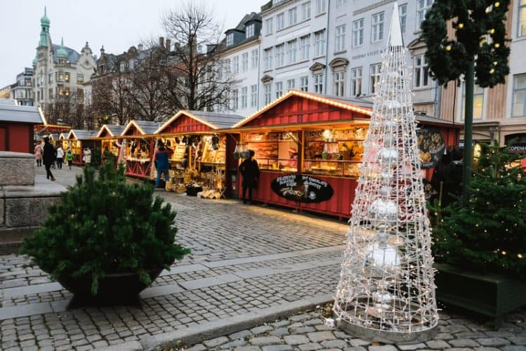 Copenhagen / Denmark - November 2019: Wooden stalls at Christmas Market Højbro Plads. Decorated booth selling street food and local craft goods during holidays for tourists. Hygge festive atmosphere.