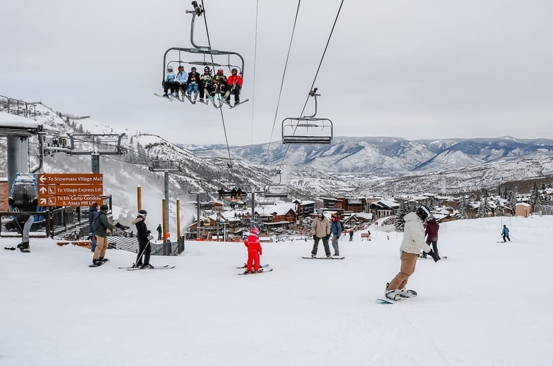 Skiers sitting on the express lift and skiing on the snow ground in Aspen Snowmass Ski Resort in Colorado