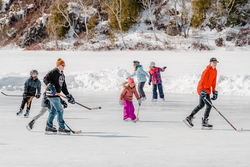 Saint John  - March 9, 2019: Adults and children practice outdoor ice hockey on a frozen lake.