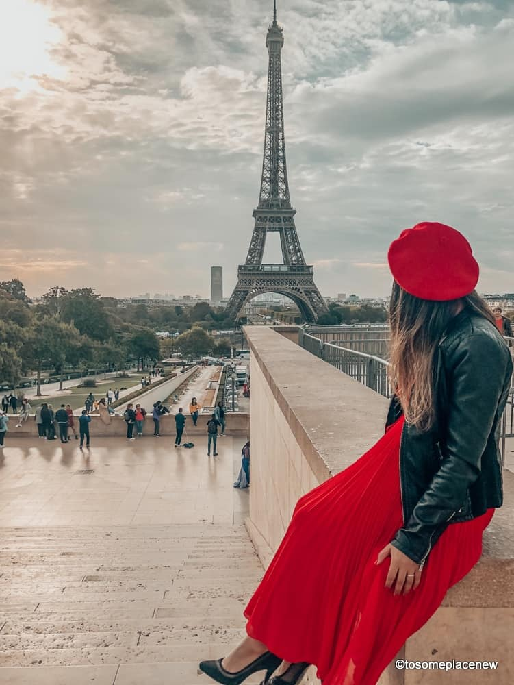 girl in a red dress admiring the Eiffel Tower in one day in Paris