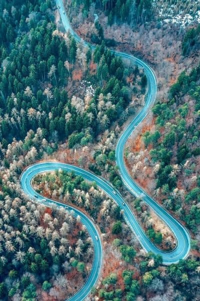 aerial view of winding road from high mountain pass with trees in Transylvania