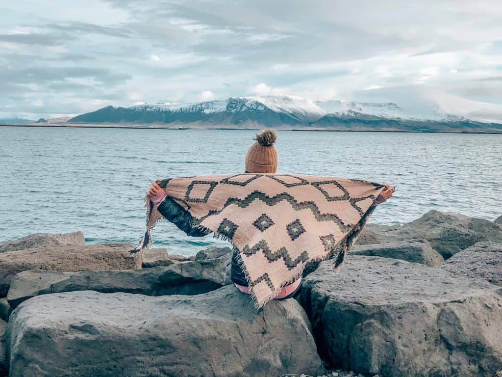 Girl in Reykjavik Harbour with mountains - Akrafjall (west) and Mount Elsa (east).