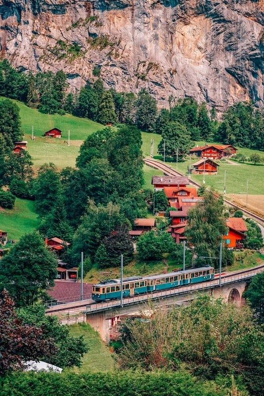 Vintage train going through the Lauterbrunnen valley located in the Swiss Alps near Interlaken, Switzerland.
