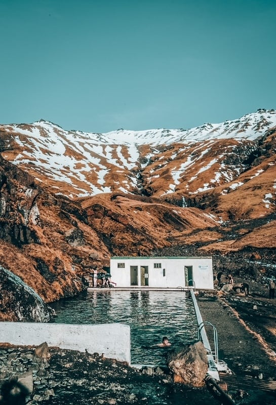 Swim in the Seljavallalaug pool, with snowy backdrop