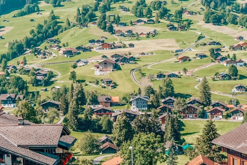 The picturesque Swiss town of Grindelwald. Traditional wooden chalets in summer, in front of the North side of the Eiger mountain surrounded by bright green pastures